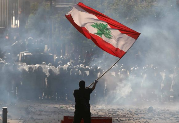 A demonstrator waves the Lebanese flag in front of riot police during a protest in Beirut, Lebanon, August 8, 2020. REUTERS/Goran Tomasevic     TPX IMAGES OF THE DAY